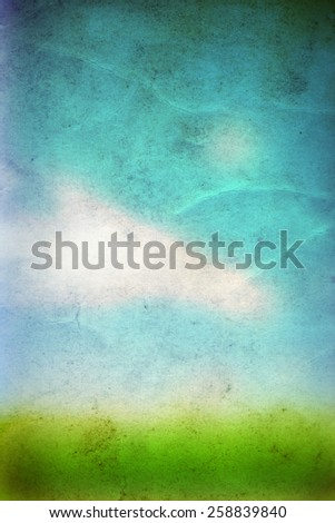 Concept or conceptual green fresh summer or spring grass field over a blue sky background on a vintage old paper, metaphor to nature, season, rural, outdoor, environment, pasture, growth conservation - stock photo