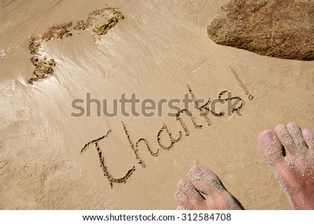 Concept or conceptual hand drawn thanks! text carved in a golden sandy beach with water, summer background with feet on exotic island, metaphor to gratitude, message, travel, tourism or vacation