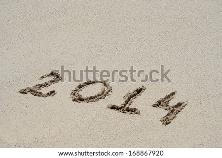 Concept or conceptual hand made or handwritten 2014 year text in sand on a beach in an exotic island