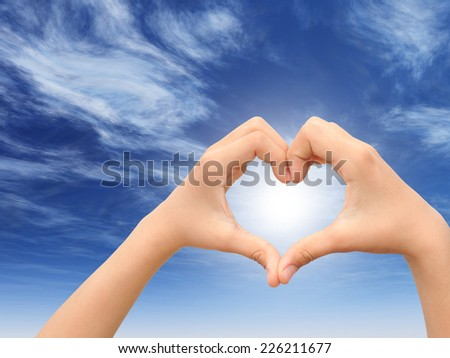 Concept or conceptual heart shape or symbol made of human or woman and man hand over a sky at blue sunset background, metaphor to love, valentine, romantic, couple, wedding, romance, summer or sunrise