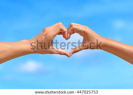 Concept or conceptual human male or man and woman hands in love, symbol of heart over blue sky background