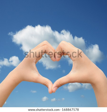 Concept or conceptual human male or man and woman hands in love, Valentines shape or symbol of heart over blue sky background,metaphor to romance,romantic,wedding,honeymoon,holiday,vacation or couple