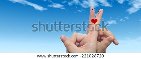 Concept or conceptual human or female hands with two fingers painted with a red heart and smiley faces over blue sky background for valentine, romantic, love, couple, young, family or wedding - stock photo