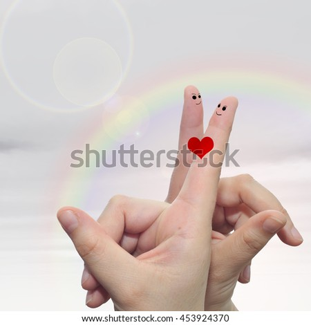 Concept or conceptual human or female hands with two fingers painted with a red heart and smiley faces over rainbow sky background  for valentine, romantic, love, couple, young, family or wedding - stock photo