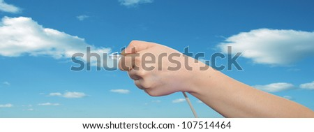 Concept or conceptual human or man hand holding a internet or data cable in clouds over the blue sky, as a metaphor for plug,connection,technology,share,network,mobility,connectivity or communication - stock photo