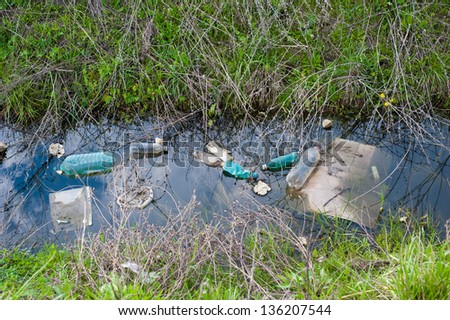 Concept or conceptual unhygienic polluted river,sewage or dirty water and grass with waste,trash and dump background,metaphor to pollution,environment,ecology,contamination,recycle,damage old problem - stock photo