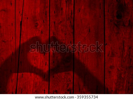 Concept or conceptual Valentine human man and woman hands silhouette as heart or love symbol on old red wood background, metaphor to romantic, romance, relationship, young, couple, wedding or lover - stock photo