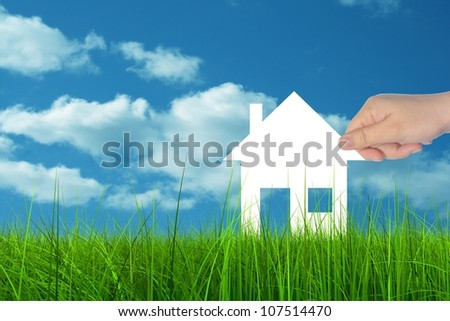 Concept or conceptual White paper house held in hand by a man in a green summer grass over a blue sky background with clouds, as a symbol for construction, eco, ecology, loan, mortgage, property home