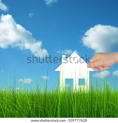 Concept or conceptual White paper house held in hand by a man in a green summer grass over a blue sky background with clouds, as a symbol for construction,eco,ecology,loan,mortgage ,property or home - stock photo