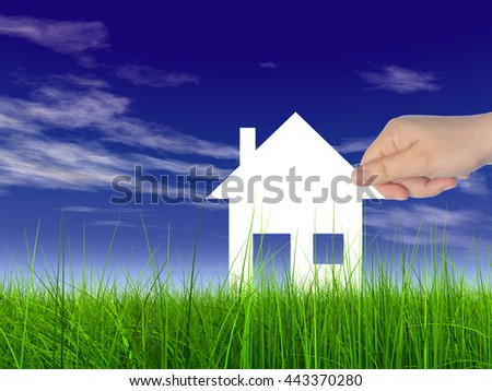 Concept or conceptual white paper house held in hand by a man in a green summer grass over a blue sky background with clouds - stock photo