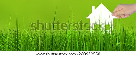 Concept or conceptual white paper house symbol held in hand by a woman in green summer grass background, metaphor to construction, eco, ecology, loan, mortgage, property, business, investment or home - stock photo