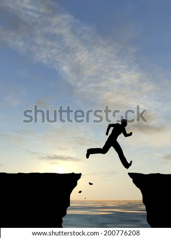 Concept or conceptual young man or businessman silhouette jump happy from cliff over water gap sunset or sunrise sky background - stock photo