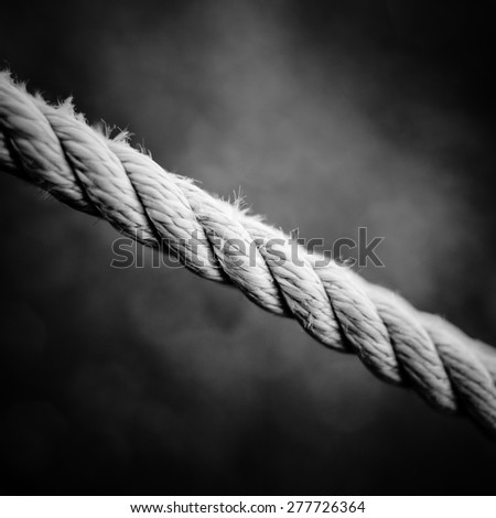 Concept: part of an old rope closeup over a dark background in monochrome tones  - stock photo