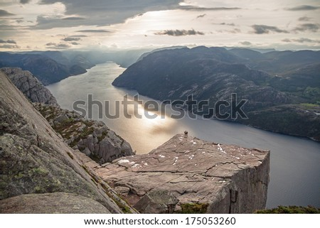 Concept people and nature; silhouettes of two people on Pulpit Rock Preikestolen, Norway.  Canon 5D. - stock photo