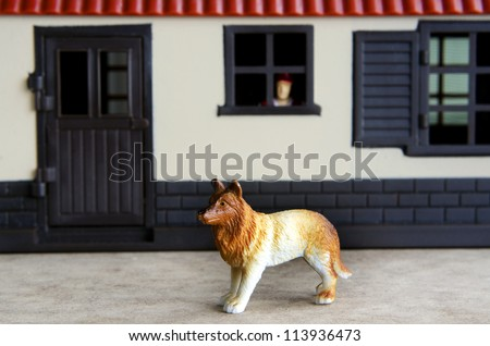 Concept photo: A toy guard dog guarding a house while a toy man watch out from his home window.
