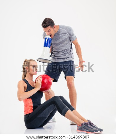 Concept photo of a coach shouting through loudspeaker on a  woman to doing exercises isolated on a white background
