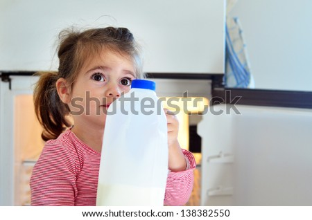Concept photo of a hungry poor little girl holds a bottle of milk at home.