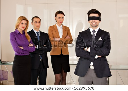 concept photo of a young businessman  smiling having eyes covered, with his partners in the background, watching him with envy - stock photo