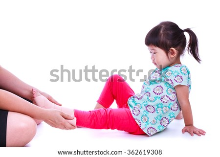Concept photo of children health and medical care. Caring nurse bandage asian girl's ankle. Mother give first aid at ankle trauma. Studio shot. Isolated on white background. - stock photo