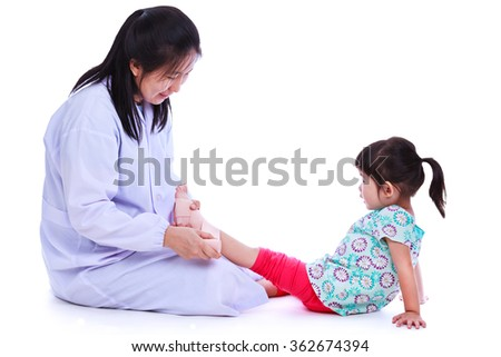 Concept photo of children health and medical care. Doctor give first aid with bandaging at girl's ankle trauma. Studio shot. Isolated on white background. - stock photo