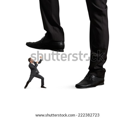 concept photo of conflict between subordinate and boss. angry young businessman punching and looking up at big palm of his boss. isolated on white background