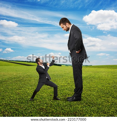 concept photo of conflict between subordinate and boss. small startled man waving his fists, big displeased businessman looking at him. photo at outdoor