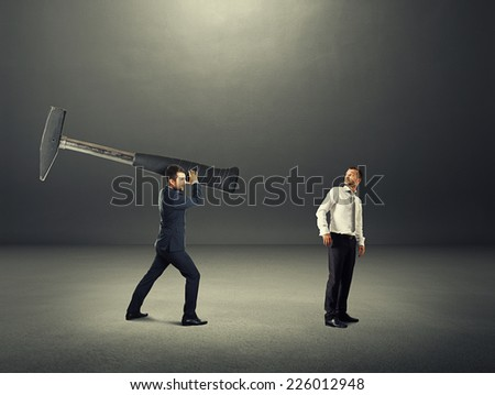 concept photo of conflict between two businessmen. amazed businessman turning around and looking at big hammer. photo in the dark room - stock photo