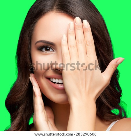 Concept photo of happy smiling young woman with one eye, closed by hand, covering part of her face, isolated over green screen chroma key background - stock photo