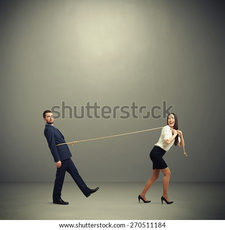 concept photo of henpecked husband. happy laughing woman pulling man on the rope and looking at him. photo in empty grey room  - stock photo