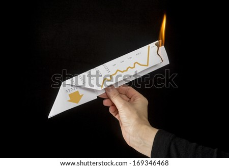 Concept photo showing a hand launching a paper airplane which is on fire and pointed down to illustrate the financial markets crashing and financial ruin - stock photo