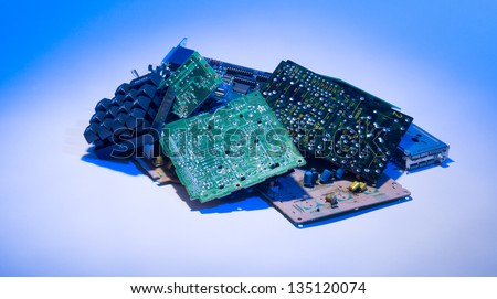 Concept photo showing digital computer parts discarded in garbage pile with blue light - stock photo
