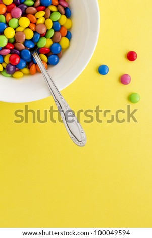 Concept photograph of a bowl full of colored chocolate buttons representing unhealthy diet. - stock photo