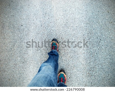Concept picture of legs walking on asphalt. - stock photo