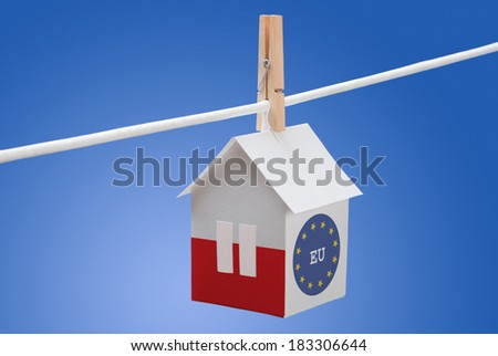 concept - poland, polish and EU flag painted on a paper house hanging on a rope - stock photo