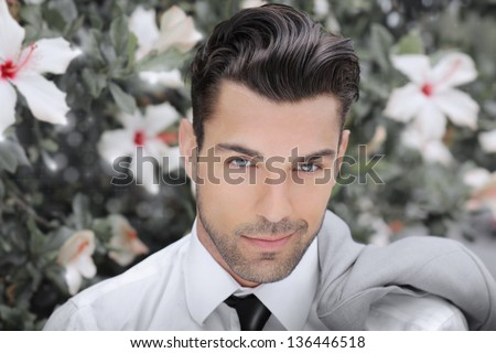 Concept portrait of a beautiful young man against background of flowers - stock photo