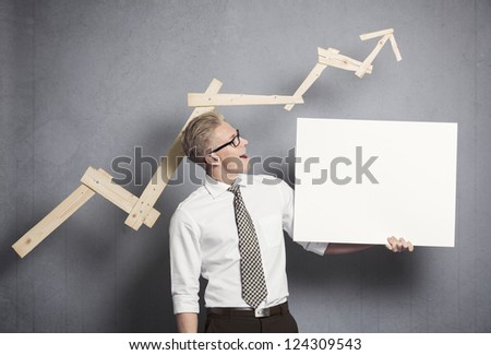 Concept: Positive business outlook. Happy confident businessman looking at empty panel in front of business graph with upward trend, isolated on grey background.