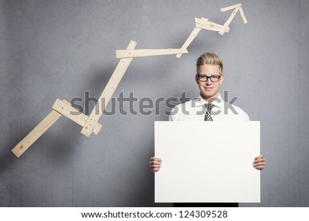 Concept: Positive business outlook. Smiling confident businessman holding empty panel in front of business graph with rising trend, isolated on grey background. - stock photo