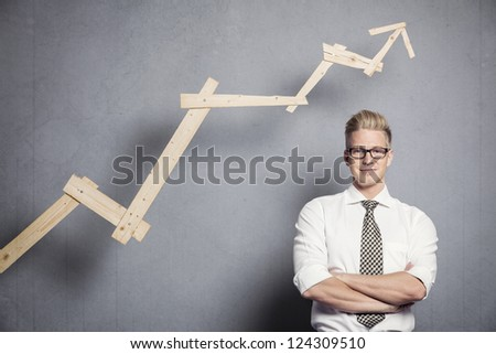 Concept: Positive business outlook. Smiling confident businessman in front of business graph with upward trend, isolated on grey background. - stock photo