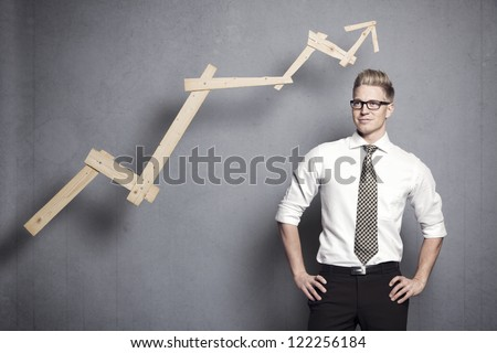 Concept: Positive business outlook. Smiling confident businessman with business vision in front of upwards pointing business graph, isolated on grey background. - stock photo
