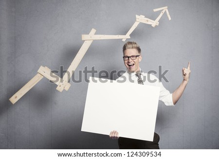 Concept: Promising business development. Cheering happy businessman holding empty panel in front of ascending business graph and pointing up, isolated on grey background. - stock photo