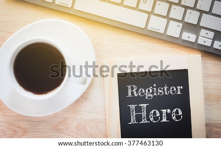 Concept Register Here message on wood boards. A keyboard and a glass coffee table.Vintage tone. - stock photo