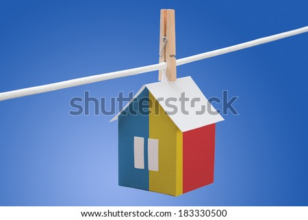 concept - Romania, Romanian flag painted on a paper house hanging on a rope - stock photo