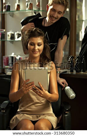Concept satisfied and happy customer. Client young girl shows her desired hairstyle hairdresser. Stylist- hairdresser and client looking at a tablet and smile- stock photo.