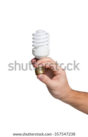 Concept saving money by using energy-saving lamps. A hand holding a lamp and a stack of coins isolated on white background