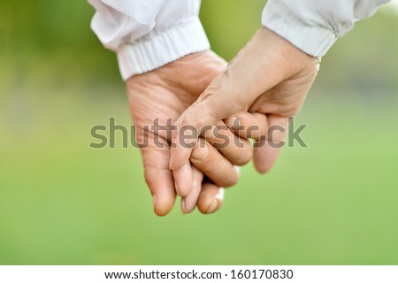Concept shoot of friendship and love of man and woman: two hands over nature - stock photo