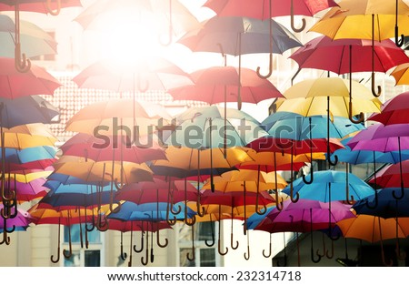 Concept shot of umbrellas of different colors in the air, with sun rays shining - stock photo
