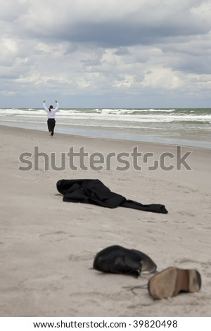 Concept shot showing a businessman leaving his clothes on a beach and running arms raised towards the sea - stock photo