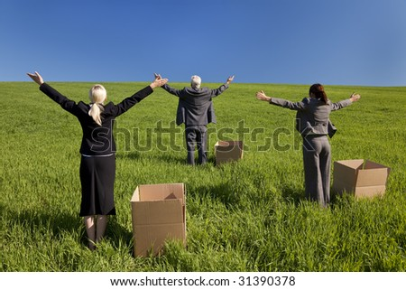 Concept shot showing three business executives standing outside boxes in a green field raising their arms towards the horizon. Environmental and business concepts, shot on location.