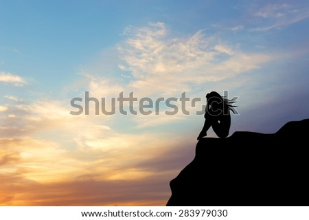 Concept .Siluet lonely girl sitting on the precipice of a cliff at sunset. design element - stock photo