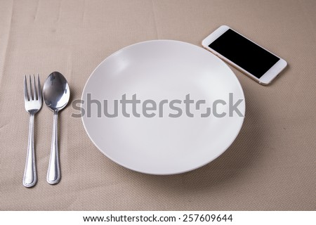 Concept smartphone and empty dish on table. - stock photo
